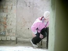 Sporty girl pissed in the old building ruins